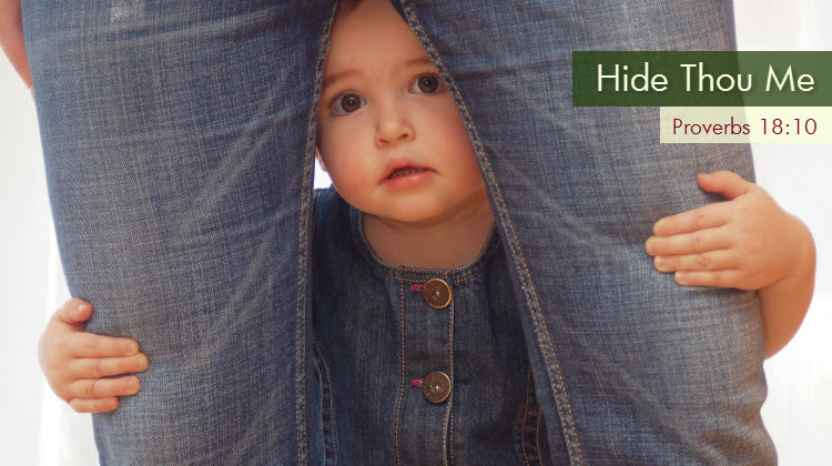 child hiding behind parent's legs
